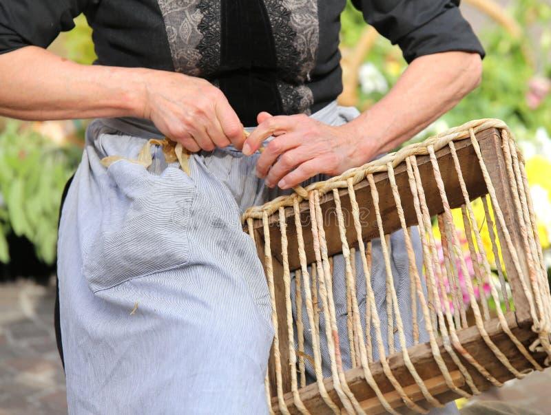 mãos de uma mulher adulta quando torção a palha para criar um feito a mão imagem de stock royalty free
