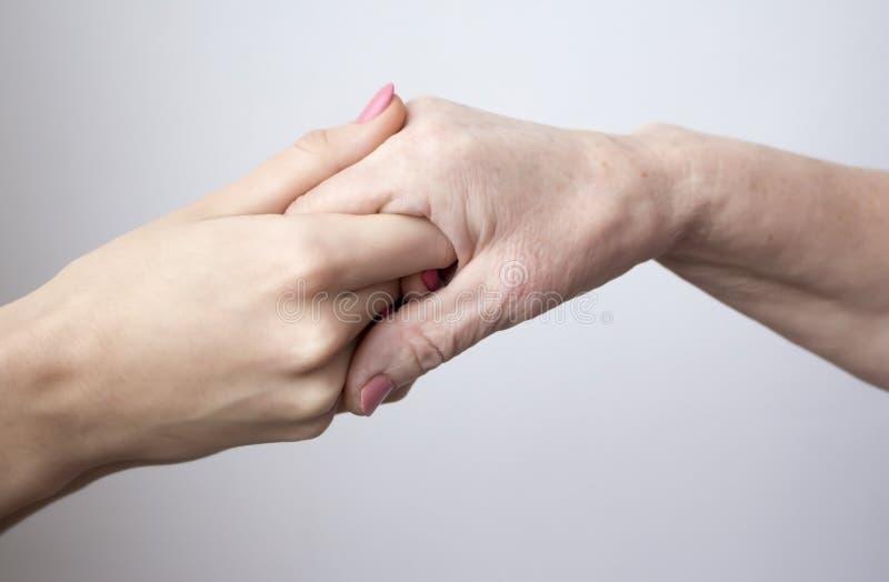 Mãos de uma mulher idosa que guarda a moça foto de stock royalty free