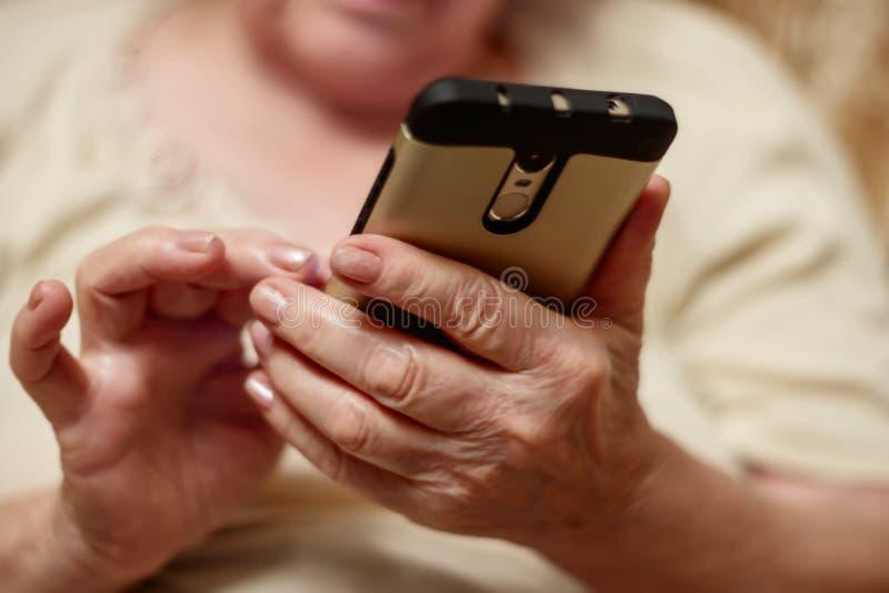 Mãos de uma mulher idosa que guarda um telefone celular imagens de stock