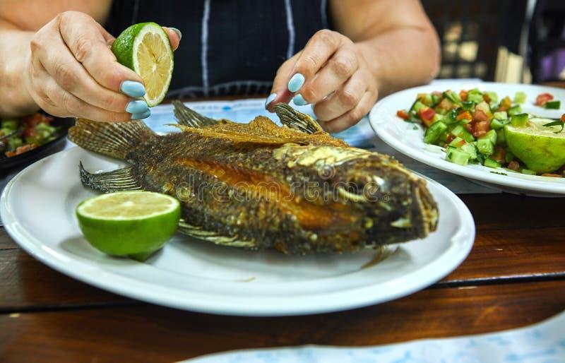 Mãos de uma mulher que guarda um limão e que derrama peixes fritados em um restaurante do escravo da placa foto de stock