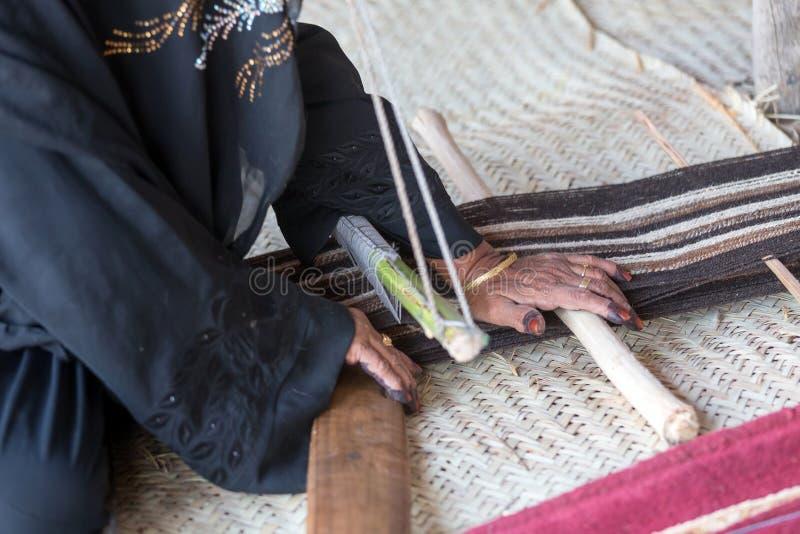 Mãos de uma senhora idosa de Emirati que usa a máquina de tecelagem tradicional fotografia de stock