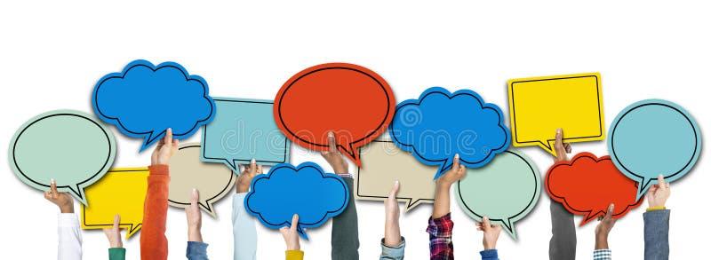 Mãos diversas que guardam bolhas coloridas do discurso ilustração stock