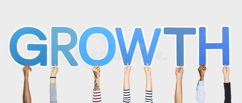 Mãos diversas que sustentam as letras azuis que formam o crescimento da palavra imagens de stock