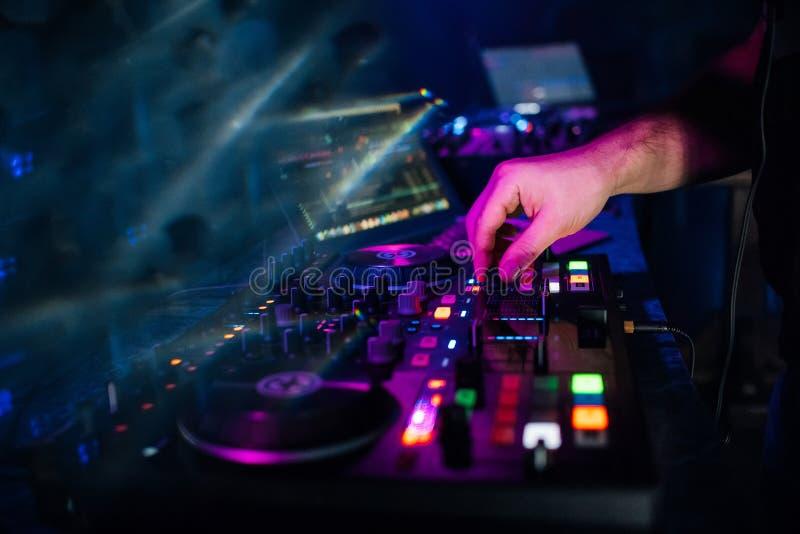 Mãos DJ que jogam e música de mistura no controlador da música em um partido imagem de stock royalty free