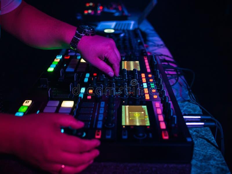 Mãos DJ que misturam e que jogam a música em um misturador profissional do controlador imagens de stock royalty free