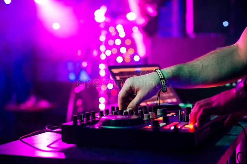 Mãos DJ que misturam e que jogam a música em um misturador profissional do controlador imagem de stock royalty free