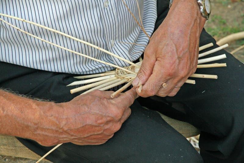 Mãos do artesão ao trabalhar o rattan para fazer um vime foto de stock