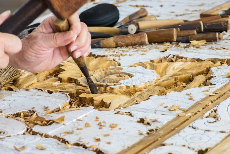 Mãos do artesão Working na cinzeladura de madeira no teste padrão floral do vintage imagens de stock