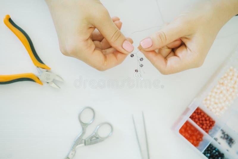 Mãos do artista com os grânulos no local de trabalho imagens de stock
