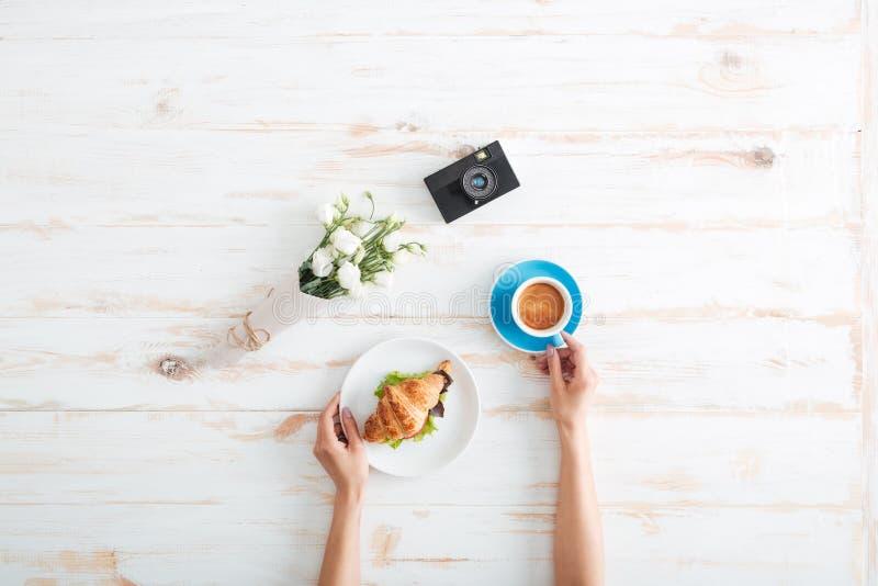 Mãos do café bebendo da mulher com o croissant na tabela de madeira fotos de stock