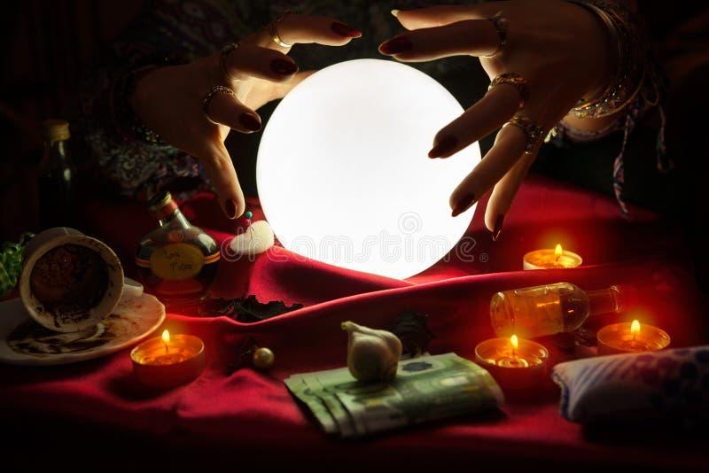 Mãos do caixa de fortuna acima da bola de cristal foto de stock