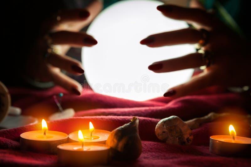 Mãos do caixa de fortuna em torno da bola de cristal fotos de stock