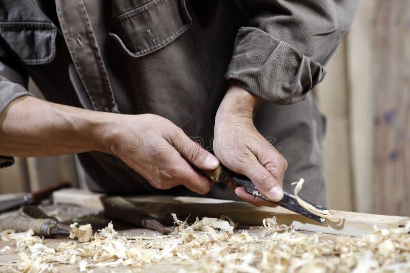 Mãos do carpinteiro com um martelo e um formão na bancada na carpintaria fotos de stock