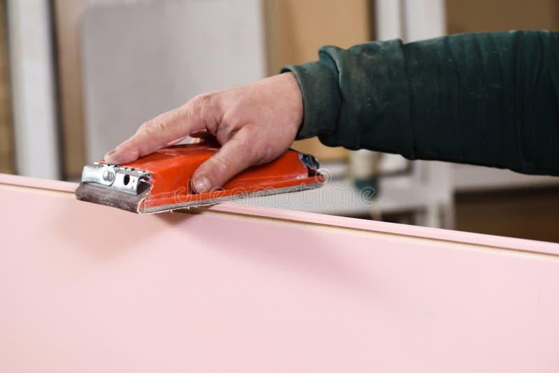 Mãos do carpinteiro que lixam o detalhe cor-de-rosa da madeira compensada com suporte da lixa fotografia de stock royalty free