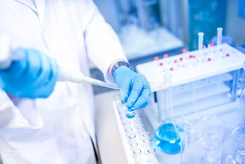 Mãos do cientista com as amostras do conta-gotas ou da pipeta, do exame e líquido azul fotografia de stock