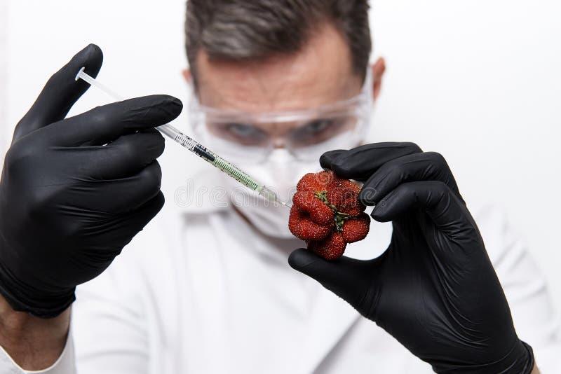 Mãos do cientista em luvas pretas com uma seringa fotografia de stock