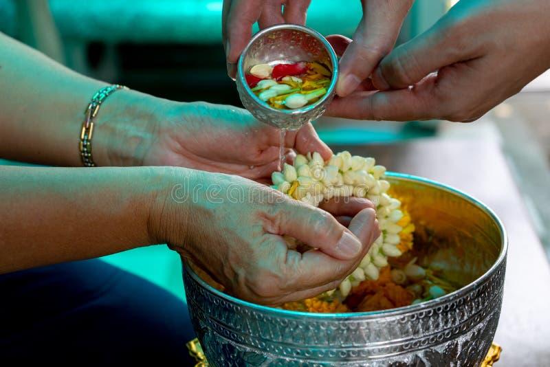 Mãos do close up da pessoa que derramam a água da bacia pequena na festão da flor nas mãos no festival de Songkran fotografia de stock royalty free