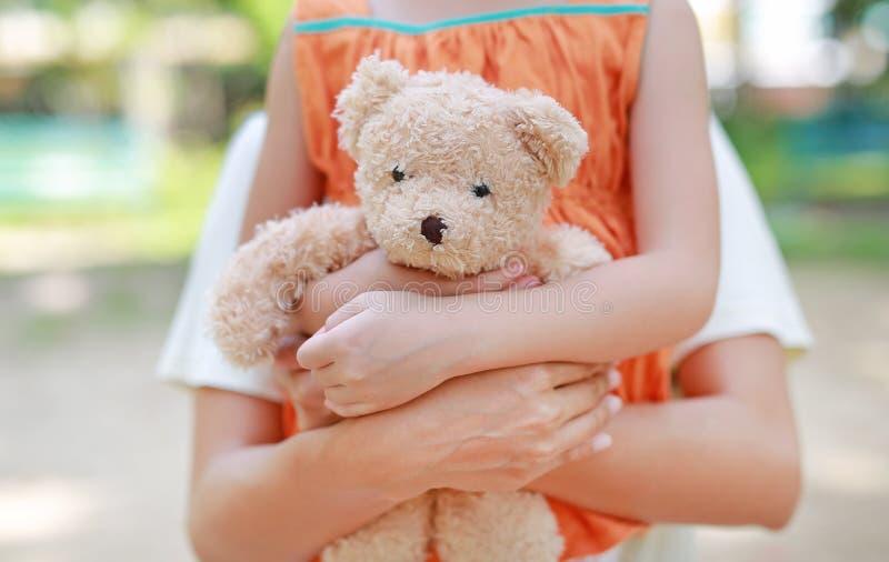 Mãos do close-up de pouca menina e de mamã da criança que abraçam o urso de peluche Boneca do afago da mãe e da filha fotografia de stock