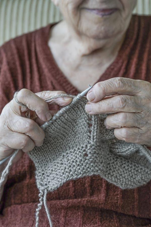 Mãos do close up de uma confecção de malhas superior da mulher imagem de stock royalty free