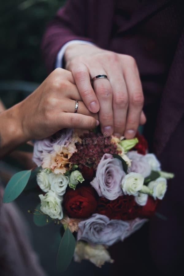 Mãos do close-up e ramalhete do casamento imagem de stock
