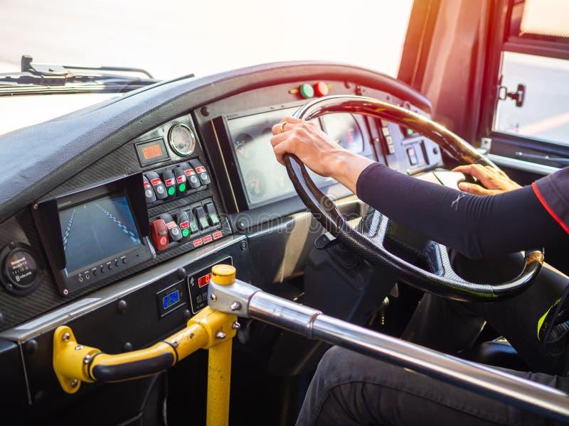 Mãos do condutor de ônibus que conduzem a camioneta expresso no aeroporto imagem de stock