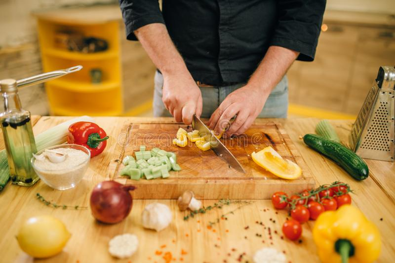 Mãos do cozinheiro chefe com o close up amarelo da pimenta dos cortes da faca imagem de stock