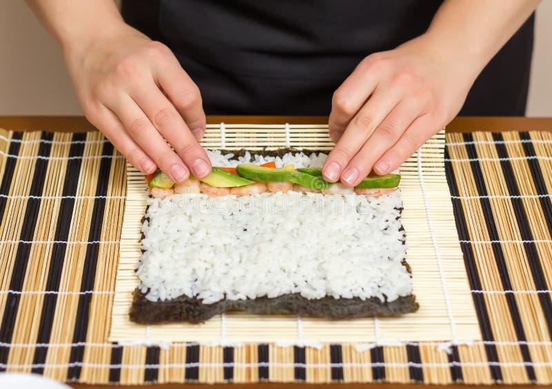 Mãos do cozinheiro chefe da mulher que rolam acima de um sushi japonês imagem de stock