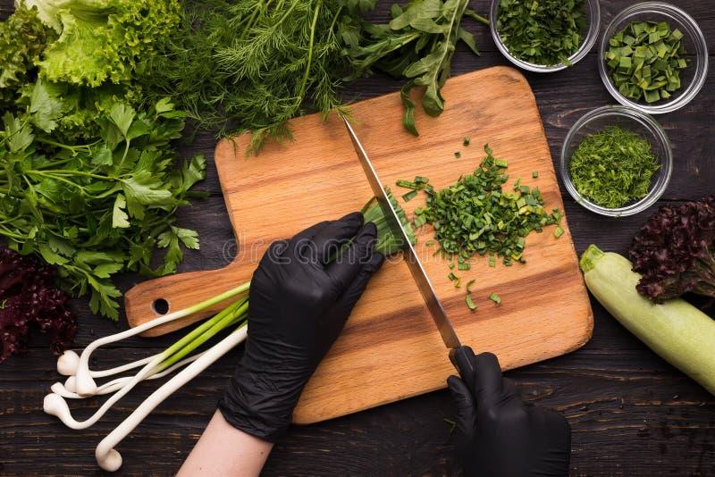 Mãos do cozinheiro chefe que cortam a cebola da mola na placa de madeira foto de stock royalty free