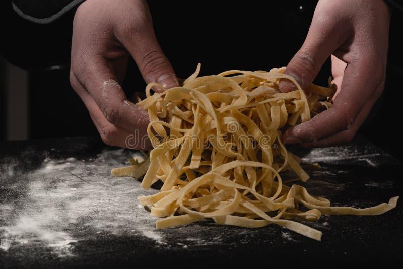 Mãos do cozinheiro chefe que fazem os espaguetes, massa, macarronetes com massa fresca na tabela preta com fotos de stock