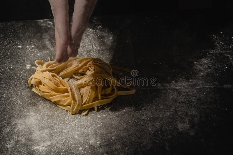 Mãos do cozinheiro chefe que fazem os espaguetes, massa, macarronetes com massa fresca na tabela preta com imagens de stock royalty free