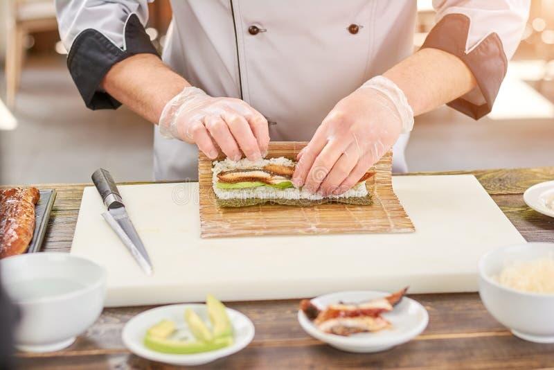 Mãos do cozinheiro que fazem o rolo de sushi japonês fotografia de stock royalty free