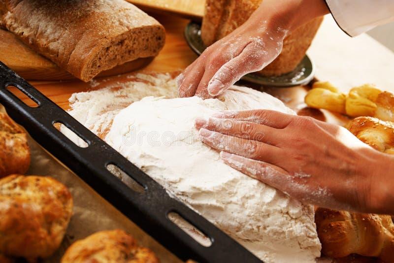 Mãos do cozinheiro que preparam a massa imagem de stock