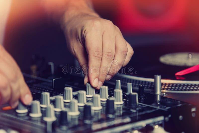 Mãos do DJ que jogam a música no clube noturno no partido fotografia de stock