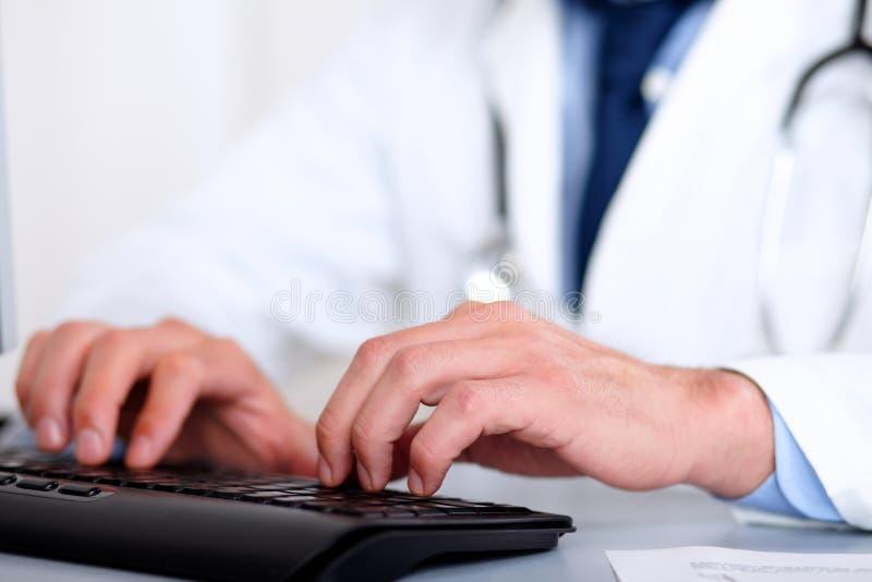 Mãos do doutor usando um computador fotos de stock