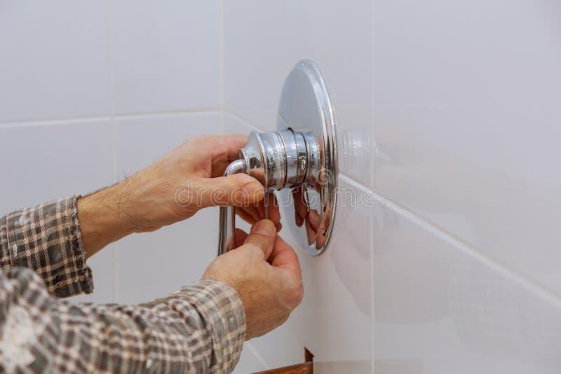Mãos do encanador que fixam o misturador do chuveiro na torneira de água moderna fotografia de stock royalty free