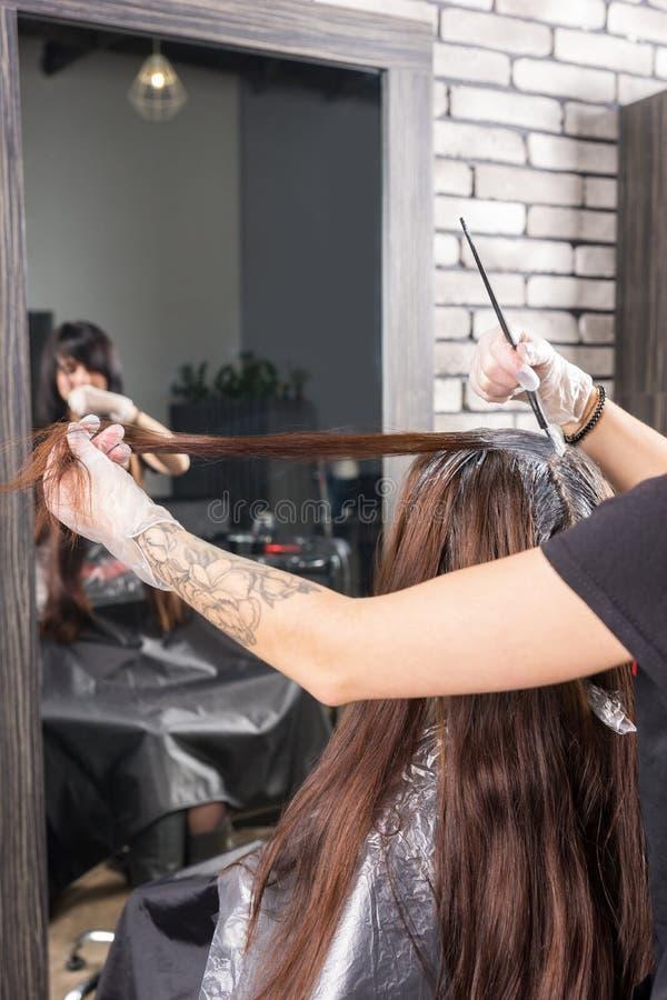 Mãos do estilista fêmea durante o processo de tingir o cabelo de w novo foto de stock royalty free