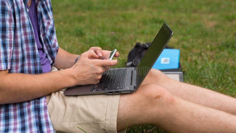 Mãos do estudante com telemóvel e portátil. fotos de stock royalty free