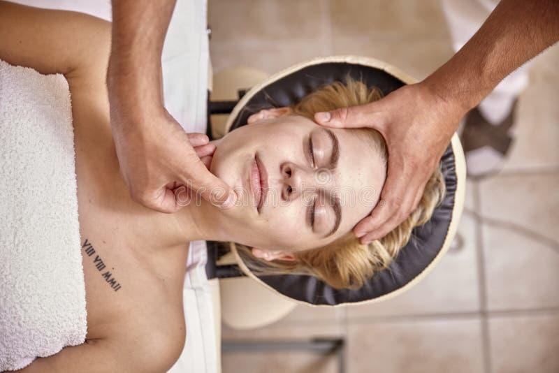 Mãos do fisioterapeuta do homem, cabeça da cara da mulher da massagem foto de stock