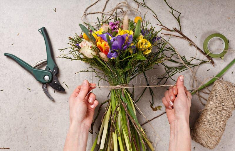 Mãos do florista que fazem o ramalhete saltar flores fotografia de stock