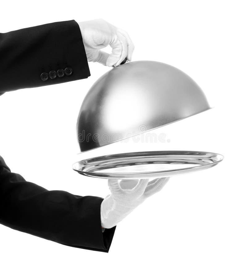 Mãos do garçom com campânula e bandeja foto de stock royalty free