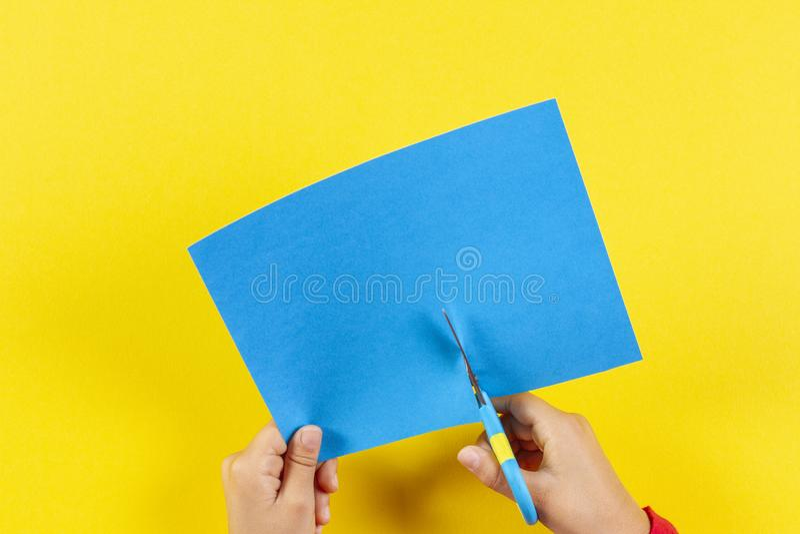 Mãos do garoto cortando papel colorido com tesoura fotos de stock royalty free