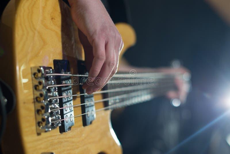 Mãos do guitarrista que jogam a guitarra sobre o preto fotografia de stock royalty free