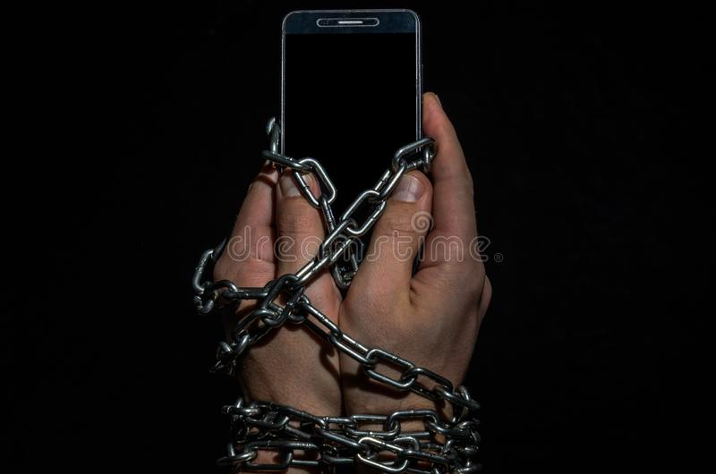 Mãos do homem acorrentadas com um telefone celular, um smartphone em um fundo preto fotografia de stock