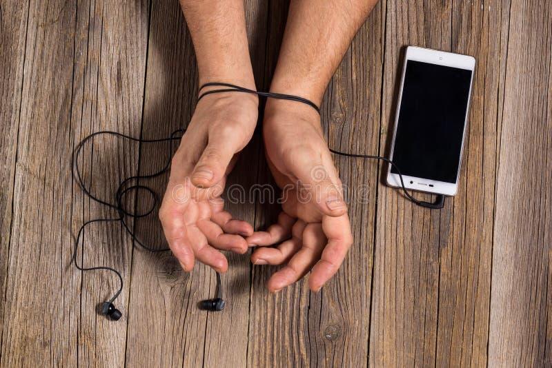 mãos do homem amarradas com auriculares do telefone, como o conceito do man& x27; dependência de s na música, tecnologia fotos de stock