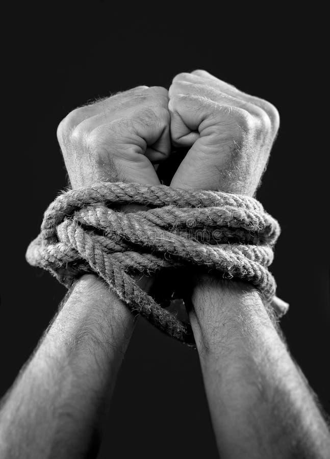 Mãos do homem branco envolvidas com corda em torno dos pulsos na vítima abusada no captiveiro, no escravo do trabalho e no respei imagens de stock