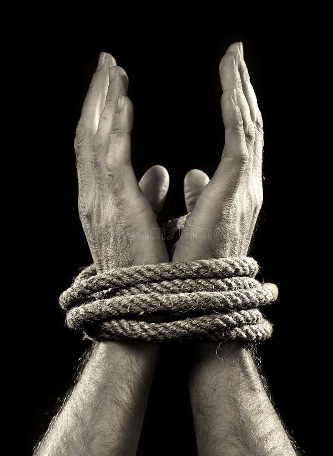 Mãos do homem branco envolvidas com corda em torno dos pulsos na vítima abusada no captiveiro, no escravo do trabalho e no respei foto de stock royalty free