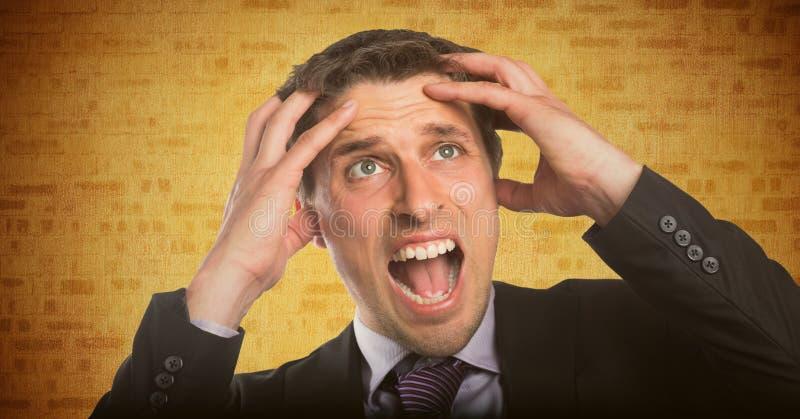 Mãos do homem de negócio na cabeça contra a parede de tijolo amarela imagem de stock