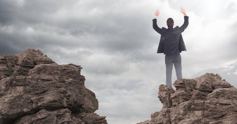 Mãos do homem de negócio no ar em rochas contra nuvens com alargamento imagens de stock royalty free