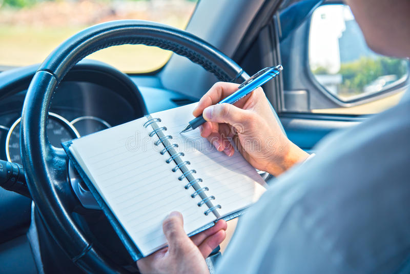 Mãos do homem de negócios com escrita da pena no caderno imagem de stock