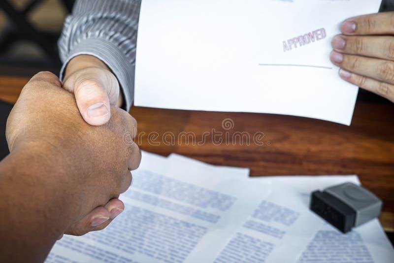 M?os do homem de neg?cios que agitam em seguida para terminar assinar e carimbar no documento de papel para aprovar o acordo de c imagem de stock